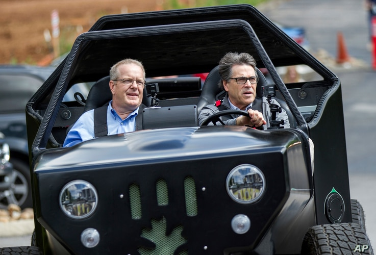 FILE - Energy Secretary Rick Perry, right, drives a 3-D printed vehicle at Oak Ridge National Laboratory's Manufacturing Demonstration Facility with staffer Craig Blue in Knoxville, Tenn., May 22, 2017.