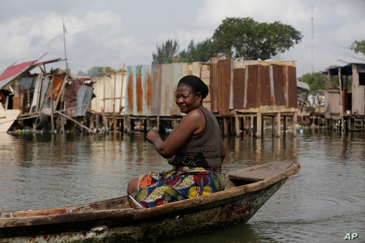 FILE - A woman peddles a canoe past residents salvaging objects from houses demolished by government officials in Otodo-Gbame waterfront in Lagos, Nigeria, March.18, 2017.