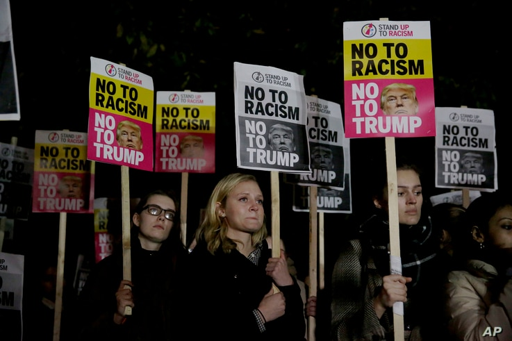 People hold placards as they take part in an anti-racism protest against President-elect Donald Trump winning the American election, outside the U.S. embassy in London, Nov. 9, 2016.