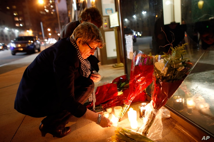 Australian native Kate Gilmore, who now resides in New York, lights candles at a makeshift memorial for South African leader Nelson Mandela outside the South African consulate, Dec. 5, 2013, in New York.