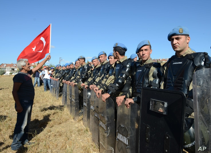 A protester argues at a paramilitary police barricade as security block thousands of people outside the Silivri jail complex in Silivri, Turkey, Aug. 5, 2013.