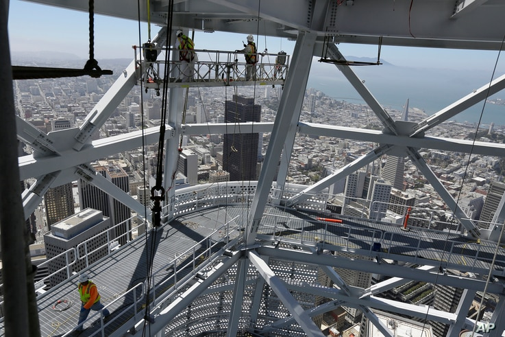 FILE - Construction crews work just below the top of the Salesforce Tower in San Francisco, July 11, 2017.