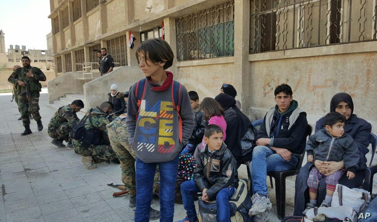 This photo released by the Syrian official news agency SANA, shows Syrian civilians, who fled fighting between the Syrian government forces and rebels, at an army checkpoint, in eastern Ghouta, a suburb of Damascus, Syria, March 13, 2018.