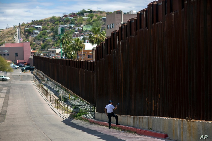 In this April 1, 2017, photo, a man in Nogales, Arizona, talks to his daughter and her mother who are standing on the other side of the border fence in Nogales, Mexico.