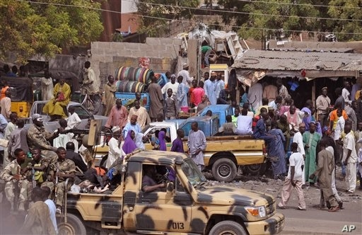 Nigerian soldiers, left, pass on the back of a armed truck as they patrol at a local market Tuesday, Jan. 27, 2015, after recent violence in surrounding areas at Maiduguri, Nigeria.  Islamic extremists are rampaging through villages in northeast Nige...