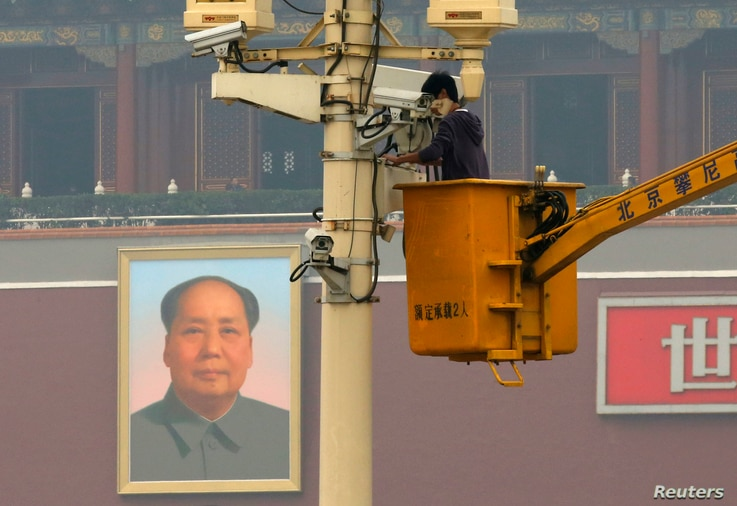 A man works on a security camera that was installed at Tiananmen Square in Beijing, November 1, 2013. China's domestic security chief believes a fatal vehicle crash in Beijing's Tiananmen Square in which five died was planned by a Uighur separatist g