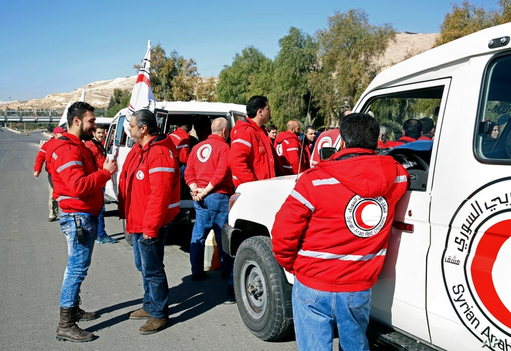 Staff from the Syrian Arab Red Crescent get ready to accompany a convoy of humanitarian aid as it waits in front of the United Nations Relief and Works Agency (UNRWA) offices before making their way into the government besieged rebel-held towns of Ma...