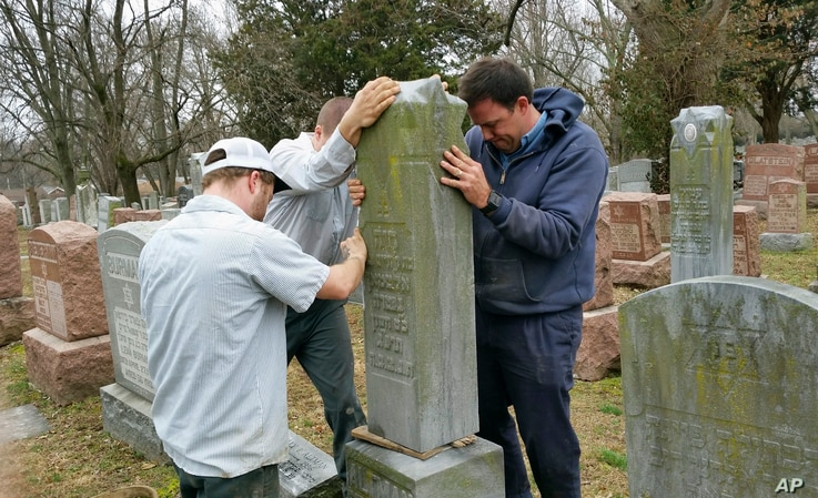 Rosenbloom Monument Co. workers hoist a headstone at the Chesed Shel Emeth Cemetery in University City, Mo., where over 150 headstones were tipped over. The cemetery is getting a show of support from volunteers, well-wishers and financial contributor...