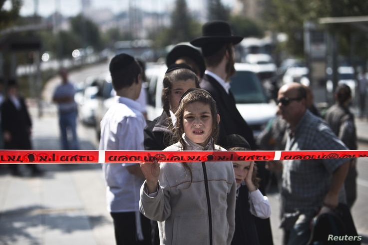 An Israeli boy stands behind the police line at the scene where a Palestinian youth stabbed and wounded a Jewish seminary student in Jerusalem, Oct. 8, 2015. The assailant was arrested at the scene, police said.