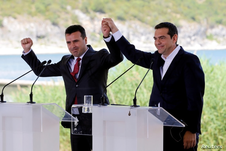 FILE - Greek Prime Minister Alexis Tsipras and Macedonian Prime Minister Zoran Zaev gesture before the signing of an accord to settle a long dispute over the former Yugoslav republic's name in the village of Psarades, in Prespes, Greece, June 17, 201...
