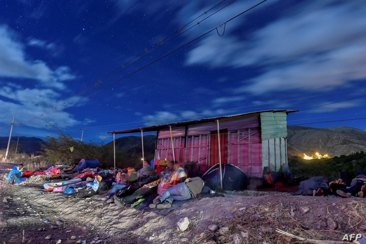 Venezuelan migrants on their way to Peru sleep along the Pan-American Highway between Tulcan and Ibarra in Ecuador, after entering the country from Colombia, on August 22, 2018.