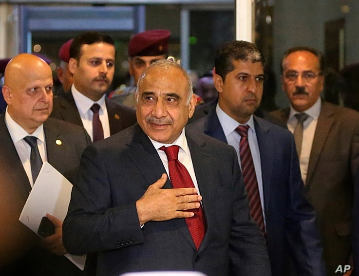 Prime Minister-designate Adel Abdul-Mahdi, center, arrives to the parliament building, in the heavily guarded Green Zone, in Baghdad, Iraq, Oct. 24, 2018.