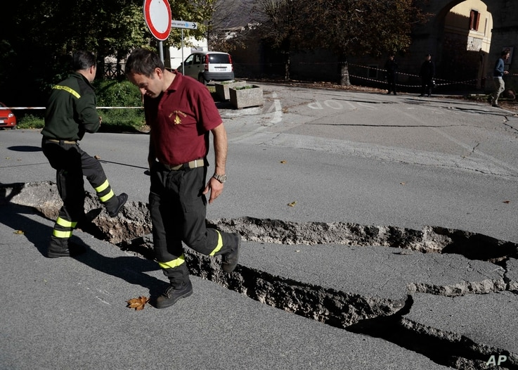 Firefighters inspect cracks in a road in Norcia, central Italy, after an earthquake with a preliminary magnitude of 6.6 struck central Italy, Oct. 30, 2016.