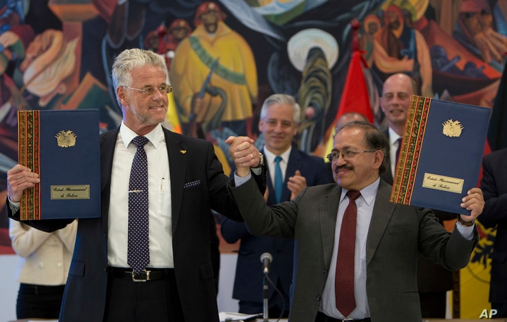 FILE - ACI Systems GmbH's President Wolfgang Schmutz from Germany, left, and manager of state company of Yacimientos Boliviano de Litio, Juan Carlos Montenegro, pose for photos during a signing ceremony in government palace in La Paz, Bolivia, Oct. 5...
