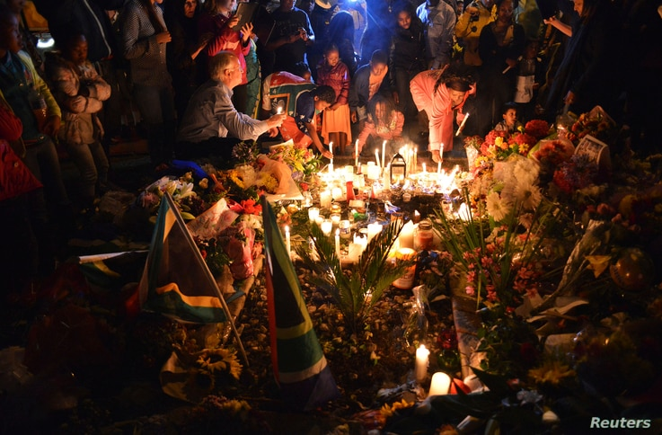 Mourners light candles for the late leader Nelson Mandela, in Johannesburg, South Africa, Dec. 6, 2013.