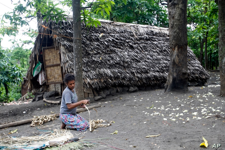 FILE - A woman weaves a mat in a village on Tanna Island in Vanuatu, June 2, 2015. Tanna Island was particularly hard hit by Cyclone Pam, which struck in March of that year. Many people in Vanuatu believed the cyclone was the latest manifestation of ...