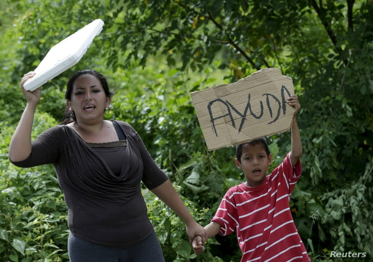 """Local residents hold up a poster along a road near the village of Canoa, April 25, 2016, after an earthquake struck off Ecuador's Pacific coast. The sign reads """"help""""."""