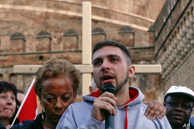 Sex abuse survivor Alessandro Battaglia, right, is hugged by survivor and founding member of the ECA (Ending Clergy Abuse), Denise Buchanan, as he speaks during a twilight vigil prayer near Castle Sant' Angelo, in Rome, Feb. 21, 2019.