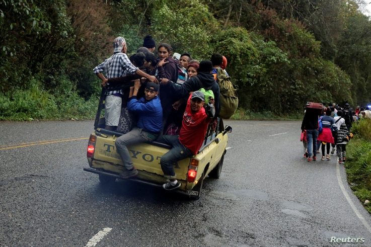 Migrants from Honduras, part of a new caravan from Central America trying to reach the United States, walk along a road as others hitch a ride in a truck, in Esquipulas, Guatemala, Jan. 16, 2019.