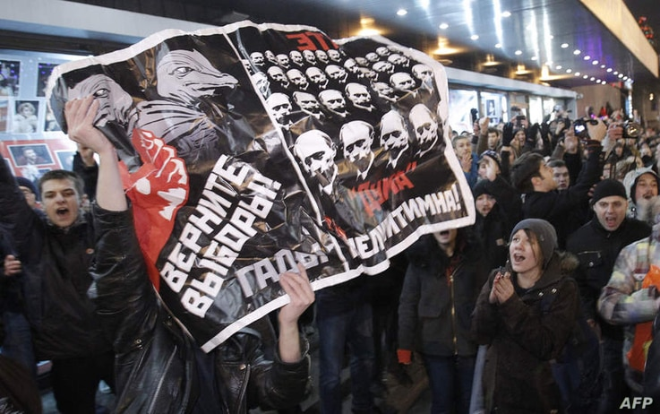 """Opposition demonstrators hold a poster reading """"Give back the elections, rascals"""" during protests against alleged vote rigging in Russia's parliamentary elections in Triumphal Square  in Moscow, Russia, Tuesday, Dec. 6, 2011. Police clashed Tuesday o..."""