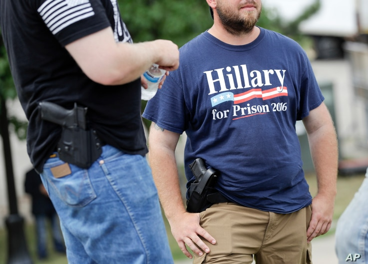 Supporters carrying side arms wait for the start of a rally for Republican presidential candidate Donald Trump at Settlers Landing Park in Cleveland, Ohio, July 18, 2016.