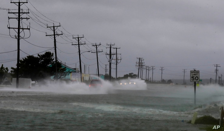 Vehicles navigate a flooded Highway 64 as wind pushes water over the road as Hurricane Arthur passes through Nags Head, N.C., Friday, July 4, 2014.