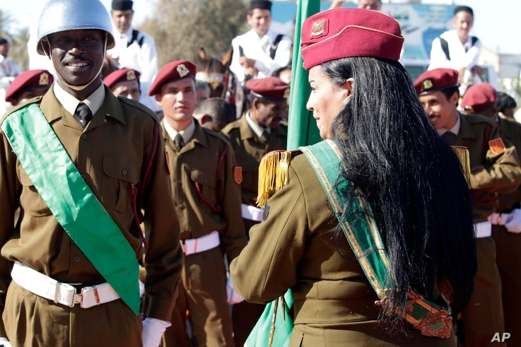 A female colonel of the Libyan Army holds the national flag as she waits with other soldiers for African leaders at Tripoli's airport, Libya, Sunday, April 10, 2011. . Envoys from the African Union, including South African president Jacob Zuma ,  are...