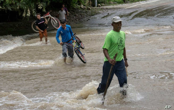 People cross a road that flooded after the passing of Hurricane Otto in Cardenas, Nicaragua, Nov. 25, 2016.