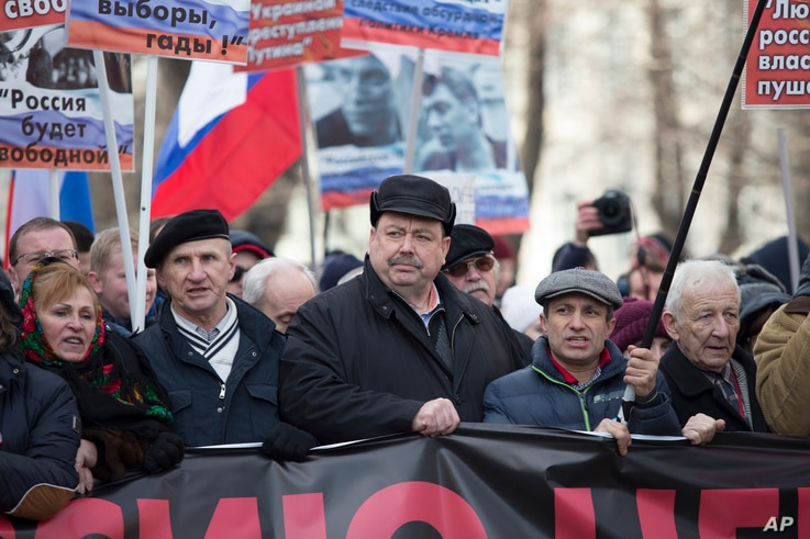 FILE - Russian former opposition lawmaker Gennady Gudkov, center, takes part in a march in memory of opposition leader Boris Nemtsov in Moscow, Russia, Sunday, Feb. 26, 2017.
