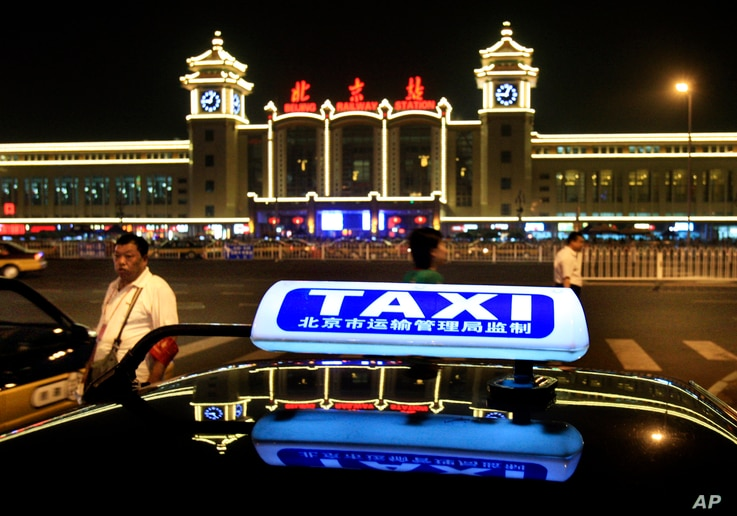 FILE - A taxi waits near the Beijing Railway Station.