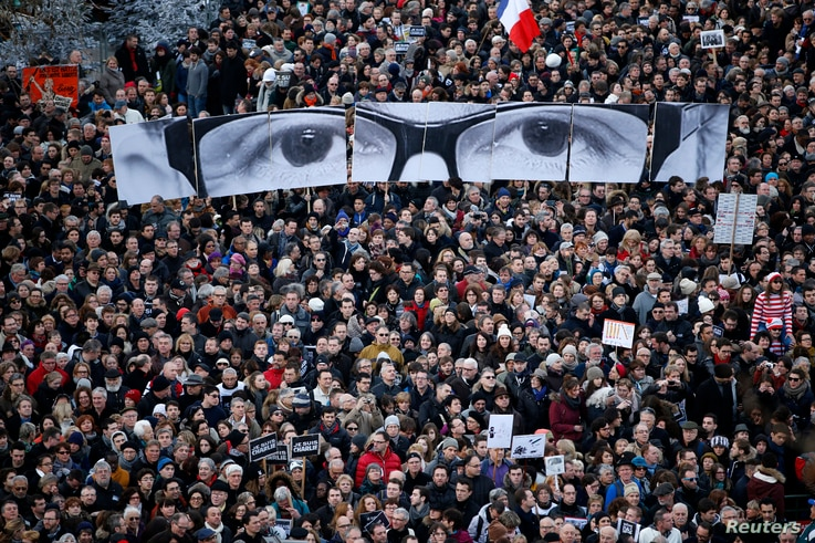 """People hold panels to create the eyes of late Charlie Hebdo editor Stephane Charbonnier, known as """"Charb"""", as hundreds of thousands of French citizens take part in a solidarity march (Marche Republicaine) in the streets of Paris January 11, 2015.  Fr..."""