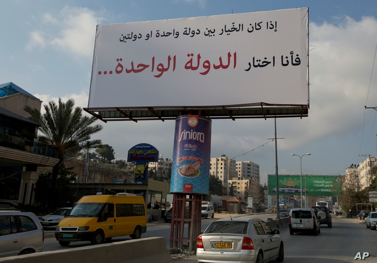 """FILE - Motorists pass a banner supporting the creation of a single state for Israelis and Palestinians that reads in Arabic: """"If I had to choose between one state and two states, I would choose the one state,"""" in the West Bank city of Ramallah, Feb. ..."""