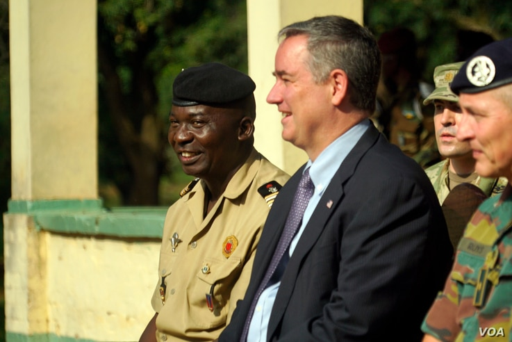 The Central African Republic's deputy chief of staff for planning, Lieutenant Colonel Ishmael Koagu, sits next to U.S. Ambassador to C.A.R. Jeffrey Hawkins during a ceremony when the ambassador turned over the keys to four cargo trucks. (Z. Baddorf/V...