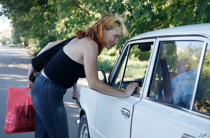 FILE - A sex worker talks to a driver on a roadside in the city of Cherkassy, 200 kilometers (124 miles) southeast of the Ukrainian capital Kyiv, July 16, 2010.