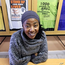 AIDS activist Vuyiseka Dubula sits beneath t-shirts in the offices of the Treatment Action Campaign in Cape Town's Khayelitsha township May 31, 2011