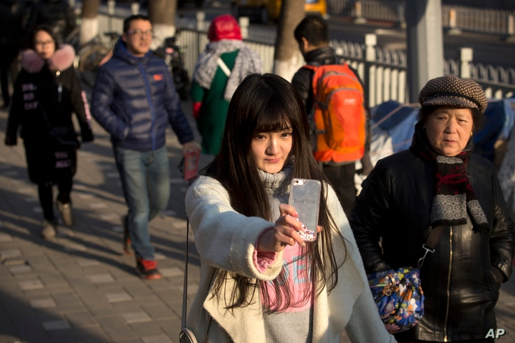 Online web performer Wang Weiying, 18, broadcasts a live stream from her smartphone as she walks down a street in Beijing, Feb. 28, 2016.