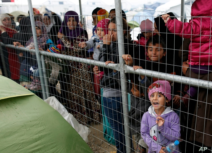 Migrants wait for food in the makeshift refugee camp at the northern border point of Idomeni, Greece, March 23, 2016.