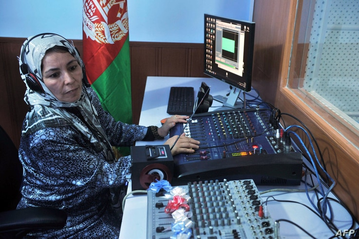 """FILE - Female Afghan journalist works in the studio of """"Shahrzad,"""" the second radio station to be dedicated to the interests of women, Herat, Oct. 14, 2012."""