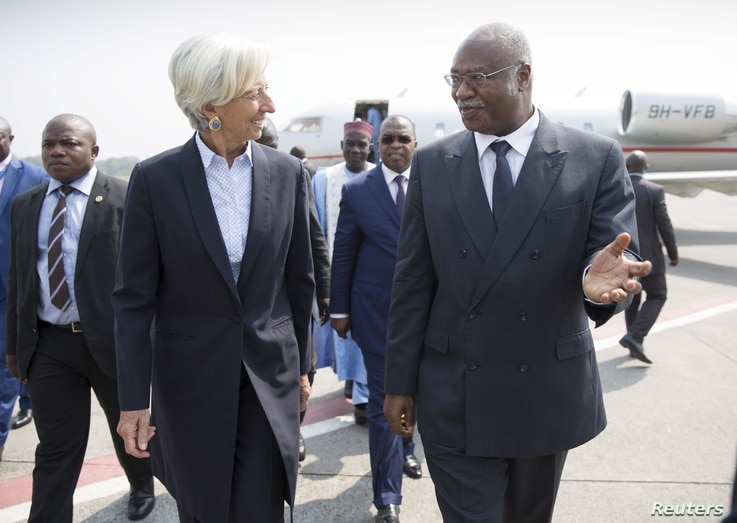 IMF Managing Director Christine Lagarde is greeted by Cameroon's Prime Minister Philemon Yang, right, upon arriving at the Yaounde airport, Jan. 7, 2016.