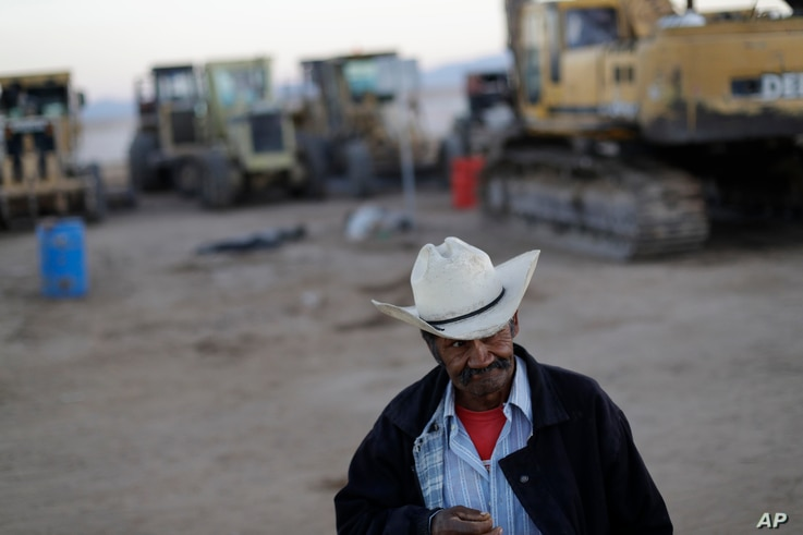 Security guard Jose Guadalupe Gonzalez walks past the remaining heavy machinery at the Ford construction site, one day after the auto company cancelled their plant's construction.
