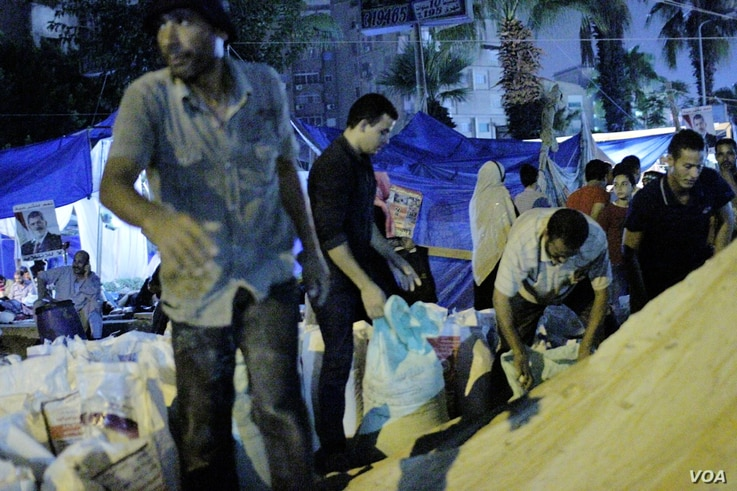 At the edge of the pro-Morsi camp, men shovel sand in bags to pile around their tent city, July 29, 2013.  Protesters say they believe sand will stop bullets better than the brick walls they erected over the weekend.  (Hamada Elrasam/VOA)