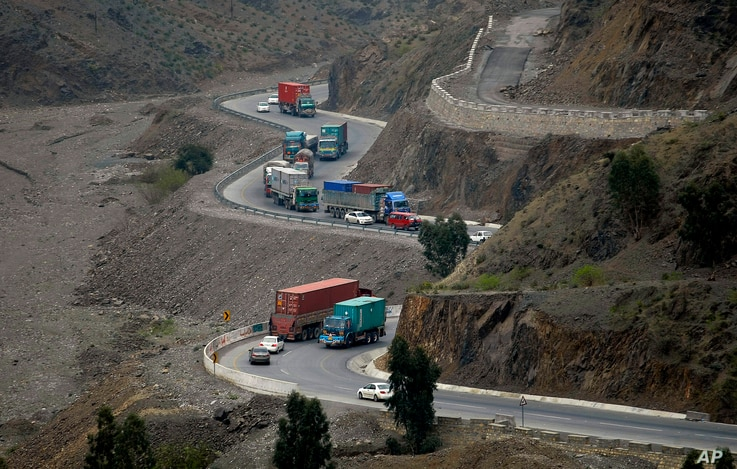 Trucks carry goods on its way to neighboring Afghanistan through the Khyber Pass in Pakistani tribal area, March 21, 2017. A Pakistani border official says hundreds of trucks have crossed into Afghanistan from Pakistan after the border reopened for t...