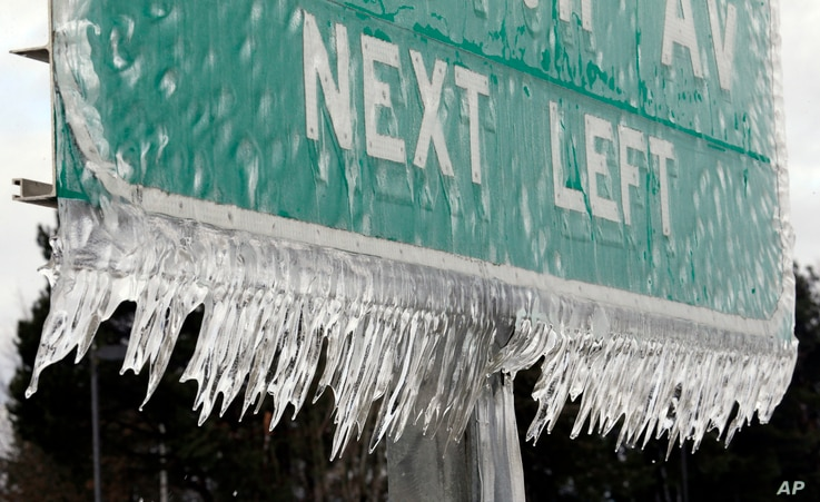 Icicles, formed by freezing rain and stiff winds, hang from a road sign along Interstate 84 in Troutdale, Ore., Jan. 18, 2017.