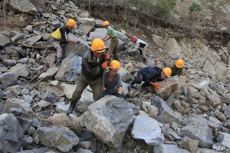 FILE - Workers repair the flood-damaged train track between Sinjon and Kanphyong train stations, North Hamgyong Province, North Korea, Sept. 16, 2016. Amid recent nuclear tensions, Pyongyang is struggling to secure aid for victims of flooding that oc...