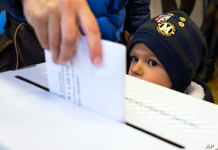 A child looks at a ballot being cast at a polling station in Zagreb, Croatia, Nov. 8, 2015.