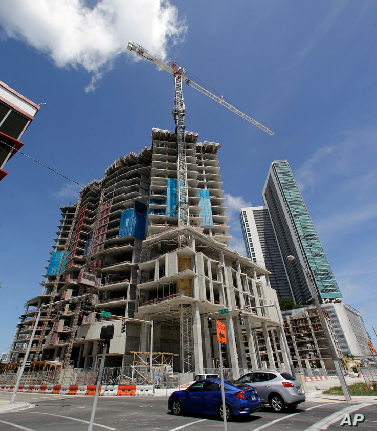 A high-rise building under construction is shown next to a high-rise condominium building, Sept. 7, 2017, in downtown Miami.