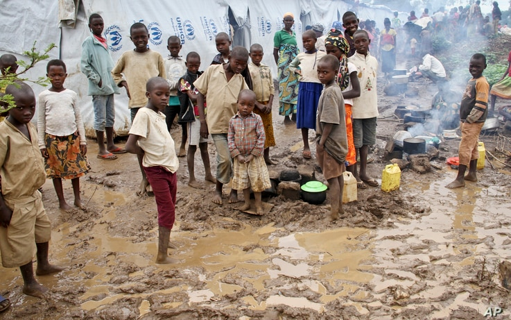 FILE - Burundian refugee children stand in the mud near to tents holding hundreds of other refugees who have fled from Burundi, at the Gashora refugee camp, in the Bugesera district of Rwanda, April 21, 2015.