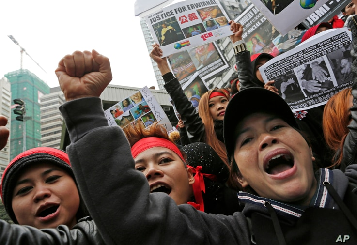 FILE - Domestic helpers and their supporters shout slogans while holding pictures of 23-year-old Indonesian maid Erwiana Sulistyaningsih during a protest in Hong Kong, Jan. 19, 2014. The Indonesian maid was allegedly brutally tortured by her employer...