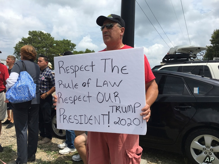 A man holds a sign supporting President Donald Trump while joining a group of pro-Trump demonstrators outside Suffolk Community College in Brentwood, New York., July 28, 2017