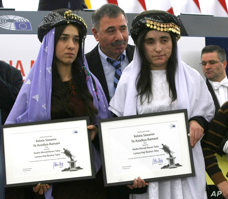 Yazidi women from Iraq, Nadia Murad Basee, left, and Lamiya Aji Bashar, pose with their award after receiving the European Union's Sakharov Prize for human rights at the European Parliament in Strasbourg, France, Dec. 13, 2016.